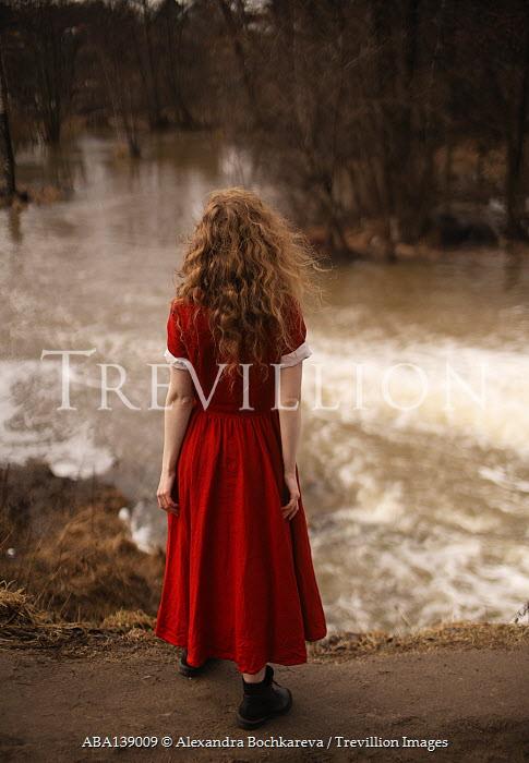 Alexandra Bochkareva WOMAN IN RED DRESS STANDING BY RIVER