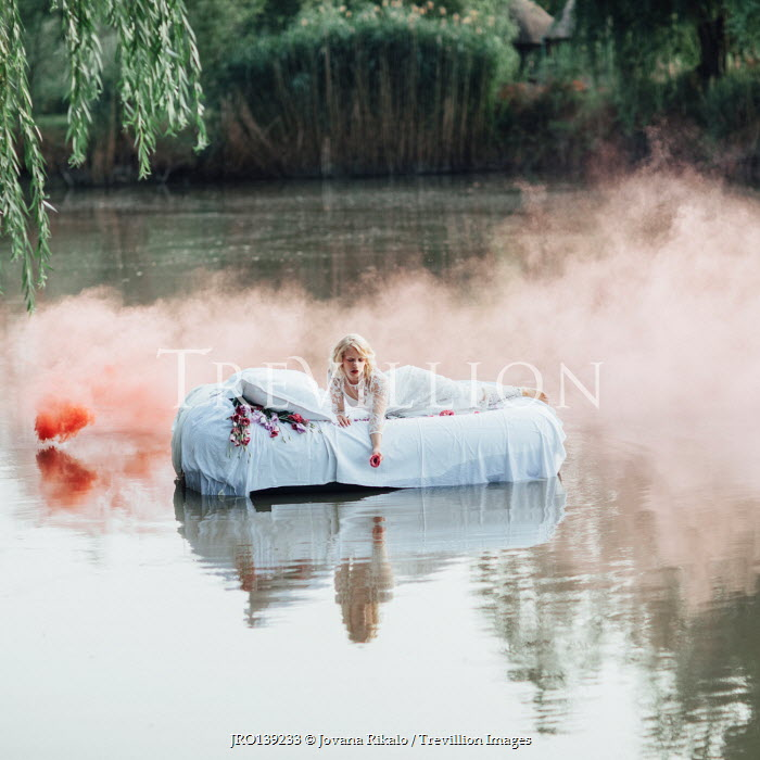 Jovana Rikalo BLONDE WOMAN ON BED IN RIVER WITH RED SMOKE