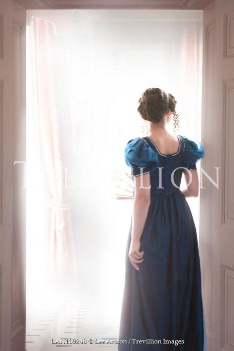 Lee Avison regency woman in blue empire line dress at a doorway
