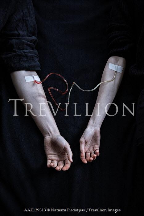 Natasza Fiedotjew blood transfusion from man's hand to woman's hand lying down