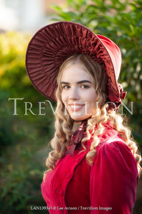 Lee Avison pretty blond regency woman with red coat and bonnet smiling to camera