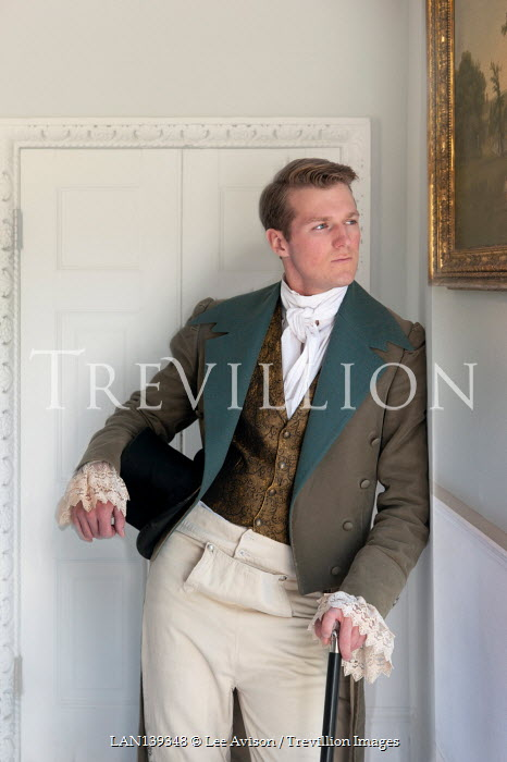 Lee Avison regency gentleman holding a top hat and cane indoors