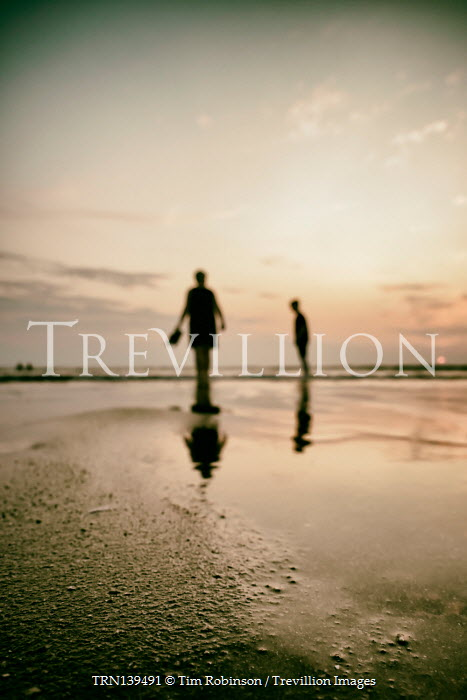 Tim Robinson SILHOUETTED COUPLE STANDING ON BEACH AT SUNSET