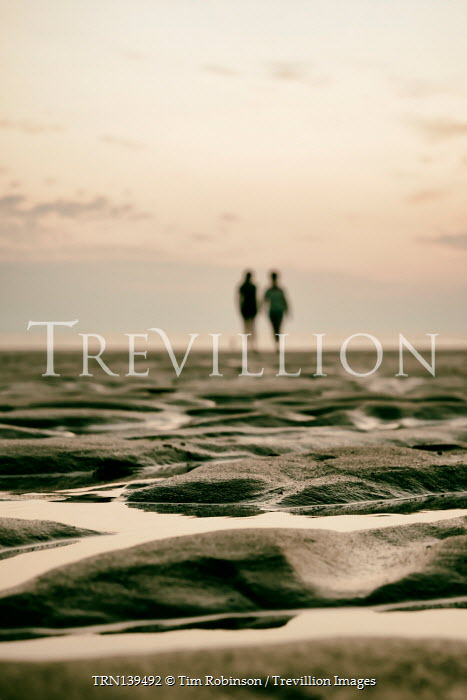 Tim Robinson DISTANT COUPLE WALKING ON BEACH AT SUNSET