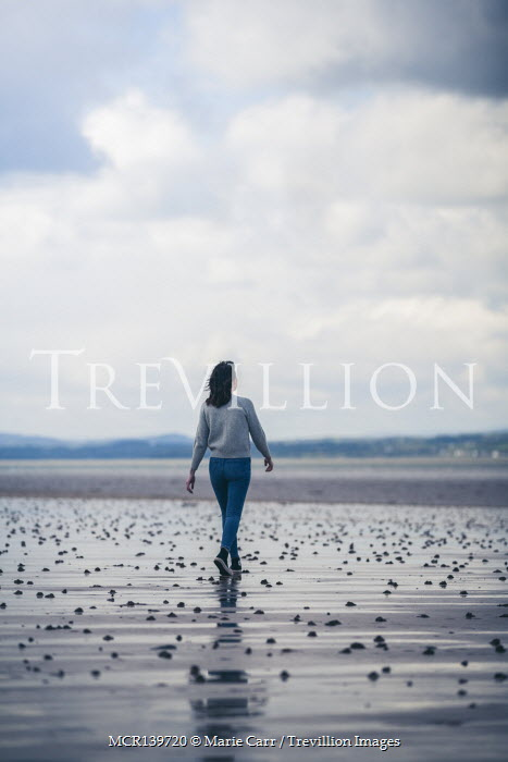 Marie Carr WOMAN IN JEANS WALKING ON BEACH
