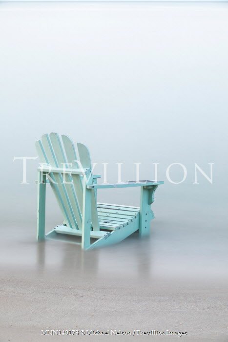 Michael Nelson WEATHERED CHAIR SINKING IN SANDY BEACH