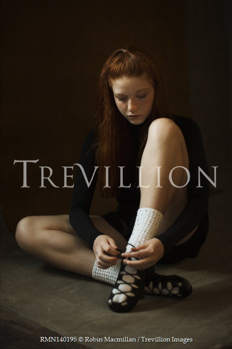 Robin Macmillan GIRL WITH RED HAIR SITTING TRYING DANCE SHOES