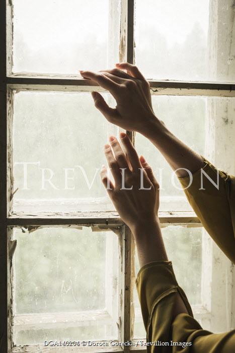 Dorota Gorecka FEMALE HANDS TOUCHING SHABBY WINDOW INDOORS