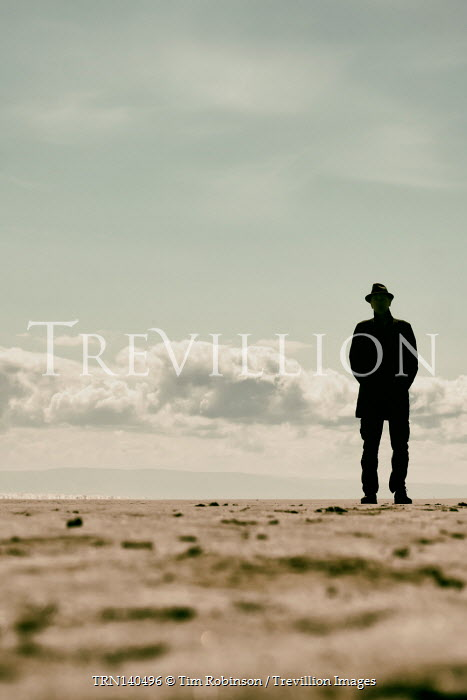 Tim Robinson SILHOUETTED MAN IN HAT ON SANDY BEACH