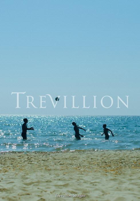 Svitozar Bilorusov THREE PEOPLE PLAYING WITH BALL IN OCEAN