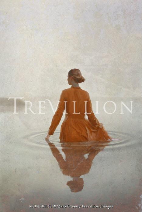 Mark Owen WOMAN IN DRESS STANDING IN RIPPLED WATER
