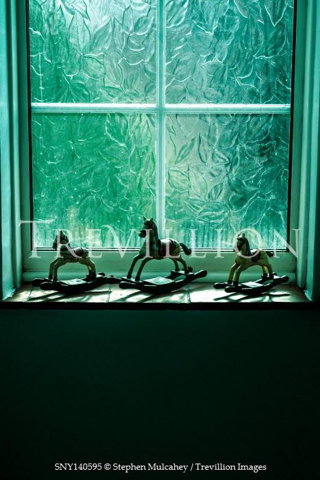 Stephen Mulcahey THREE ROCKING HORSES ON WINDOW SILL IN SHADOW