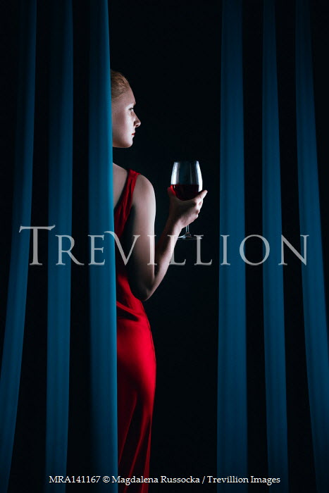Magdalena Russocka elegant woman in red dress holding glass of wine behind curtains