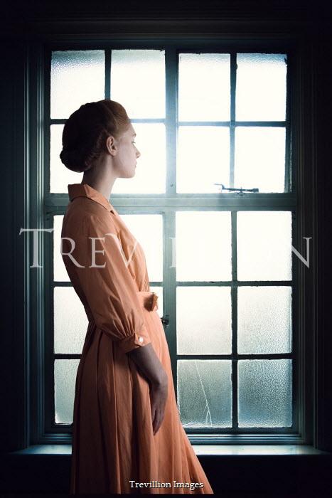 Magdalena Russocka retro woman standing by window inside