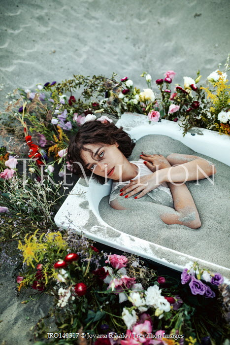 Jovana Rikalo WOMAN LYING IN BATH OF SAND WITH FLOWERS