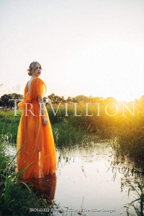 Jovana Rikalo WOMAN WITH ORANGE GOWN IN FIELD BY STREAM