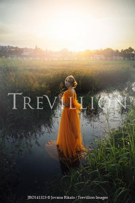 Jovana Rikalo WOMAN WITH ORANGE GOWN STANDING IN STREAM