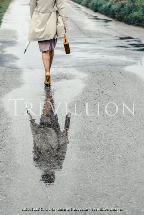 Magdalena Russocka reflection of retro woman walking through puddle