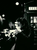 Andrew Davis MAN LIGHTING CIGARETTE BY TELEPHONE BOOTH Men