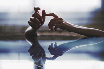 Anna Rakhvalova WOMANS HANDS ON REFLECTIVE SURFACE Women