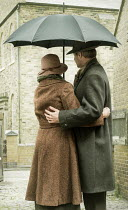 CollaborationJS vintage couple under umbrella in street Couples
