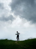 CollaborationJS man running in cloudy countryside Men