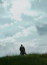 CollaborationJS 1940s man walking in cloudy field Men
