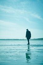 CollaborationJS A  male figure running across a beach Men