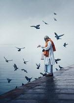 Ashraful Arefin ASIAN MAN FEEDING BIRDS BY WATER Men