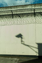 Colin Hutton PRISON WALL WITH SHADOW OF SECURITY CAMERA Miscellaneous Buildings