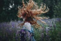 Irina Orwald WOMAN SWINGING RED HAIR IN FIELD Women