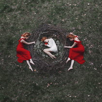 Jovana Rikalo THREE WOMEN LYING WITH NEST IN FIELD Groups/Crowds