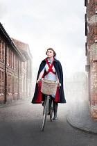 Lee Avison 1940s nurse in uniform riding a bike on a terraced street of red brick houses