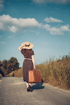 Magdalena Russocka young woman with suitcase and straw hat walking on country road