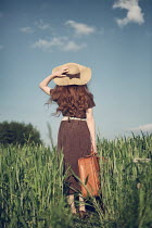 Magdalena Russocka young woman with suitcase and straw hat standing in field