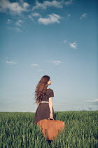 Magdalena Russocka young woman with suitcase standing in field