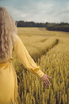 Joanna Czogala BLONDE WOMAN IN WHEAT FIELD FROM BEHIND Women