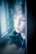 Katya Evdokimova Sad boy behind window Children