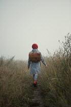 Magdalena Russocka retro girl with school bag walking in misty field