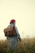 Magdalena Russocka retro teenage girl with school bag standing in misty field