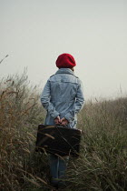 Magdalena Russocka retro teenage girl with suitcase standing in misty field