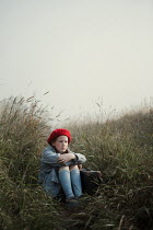 Magdalena Russocka sad young retro girl with suitcase sitting in misty field