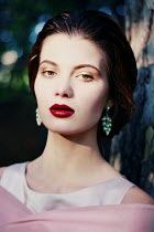 Felicia Simion Young woman with earrings and red lipstick
