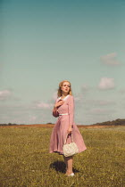 Joanna Czogala Young woman in vintage pink dress holding purse in field