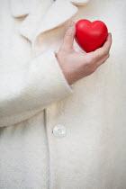 Alison Archinuk WOMAN IN WHITE COAT HOLDING RED HEART Women