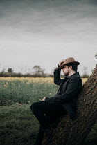 Rekha Garton MAN WITH HAT LEANING ON TREE IN COUNTRYSIDE Men