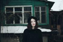 Alina Zhidovinova WOMAN STANDING OUTSIDE HOUSE WITH SNOW Women