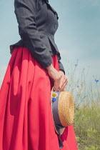 Joanna Czogala WOMAN HOLDING STARW HAT IN SUMMERY FIELD Women