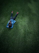 Magdalena Russocka teenage girl lying on field from above