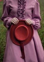 Jaroslaw Blaminsky WOMAN HOLDING RED HAT IN FIELD Women